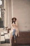 Chica joven en un sombrero y una capa en el fondo de las columnas del teatro Imagen de archivo libre de regalías