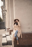 Chica joven en un sombrero y una capa en el fondo de las columnas del teatro Foto de archivo libre de regalías