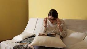 Chica joven en un suéter caliente acogedor en un invierno que iguala en casa, poniendo en los vidrios leyendo un libro Invierno C almacen de metraje de vídeo