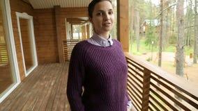 Chica joven en un suéter púrpura y vaqueros negros metrajes