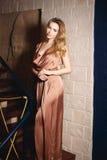 Chica joven en un vestido atractivo del oro fotos de archivo