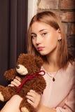 Chica joven en un vestido de la rosa con el juguete del oso Foto del estudio Foto de archivo
