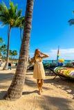 Chica joven en un vestido que camina abajo de la playa de Honolulu Waikiki imagen de archivo libre de regalías