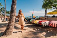 Chica joven en un vestido que camina abajo de la playa de Honolulu Waikiki imagenes de archivo