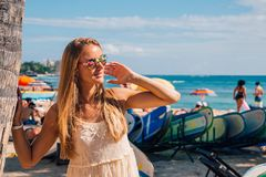 Chica joven en un vestido que camina abajo de la playa de Honolulu Waikiki Imágenes de archivo libres de regalías