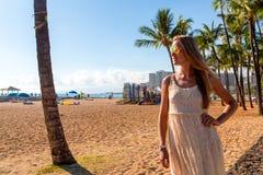 Chica joven en un vestido que camina abajo de la playa de Honolulu Waikiki Foto de archivo libre de regalías
