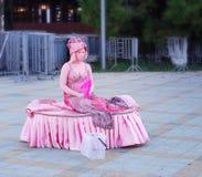 Chica joven en un vestido rosado hermoso con la cara pintada por a Foto de archivo
