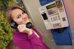 Chica joven en una cabina de teléfono Imagenes de archivo