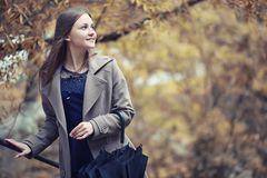 Chica joven en una capa en parque del otoño imagen de archivo libre de regalías
