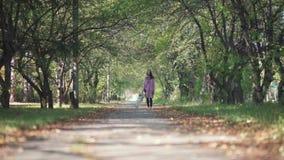 Chica joven en una capa rosada con un paseo divertido del pequeño perro en parque del otoño almacen de metraje de vídeo