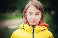 Chica joven en una chaqueta amarilla al aire libre Imagenes de archivo
