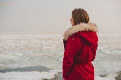Chica joven en una chaqueta roja que mira el mar helado Fotos de archivo libres de regalías