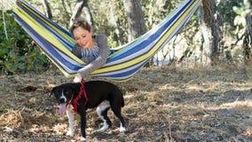 Chica joven en una hamaca que juega con el perro Foto de archivo