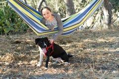 Chica joven en una hamaca que juega con el perro Fotos de archivo