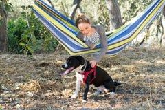 Chica joven en una hamaca que juega con el perro Fotografía de archivo libre de regalías