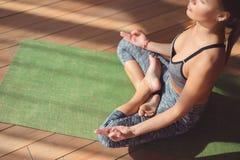 Chica joven en una posición de loto en clase de la yoga Imagenes de archivo