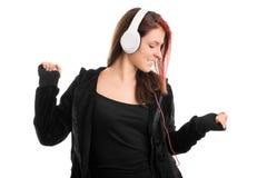 Chica joven en una sudadera con capucha que baila su canción preferida Foto de archivo