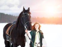 Chica joven en vestido con el caballo negro en invierno Fotografía de archivo