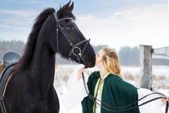 Chica joven en vestido con el caballo negro en invierno Foto de archivo libre de regalías