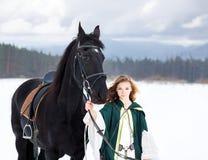 Chica joven en vestido con el caballo negro en invierno Imagen de archivo