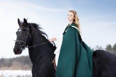 Chica joven en vestido con el caballo negro en invierno Foto de archivo