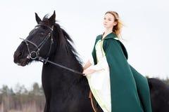 Chica joven en vestido con el caballo negro en invierno Fotografía de archivo libre de regalías