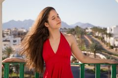 Chica joven en vestido rojo que goza en el balcón del hotel imagenes de archivo