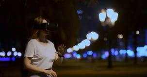 Chica joven en vidrios de la realidad virtual en una metr?poli grande almacen de video