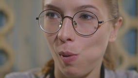 Chica joven en vidrios que come la empanada de carne en un restaurante oriental metrajes