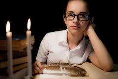 Chica joven en vidrios sobre el libro en oscuridad Fotografía de archivo