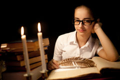 Chica joven en vidrios sobre el libro en oscuridad Imagenes de archivo