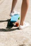 Chica joven en zapatillas de deporte en el monopatín Imagen de archivo