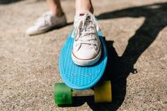 Chica joven en zapatillas de deporte en el monopatín Foto de archivo libre de regalías