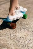 Chica joven en zapatillas de deporte en el monopatín Imágenes de archivo libres de regalías