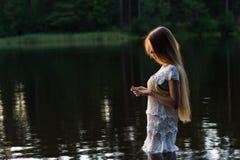 Chica joven encantadora en el vestido blanco que se coloca en agua en puesta del sol Foto de archivo libre de regalías