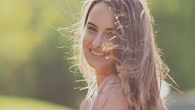 Chica joven encantadora que presenta en el parque Alegre haciendo girar La muchacha tiene pelo largo hermoso Primer almacen de video
