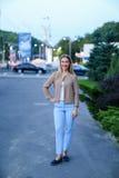 Chica joven encantadora que sonríe y que presenta a la cámara y a los soportes en f Fotografía de archivo
