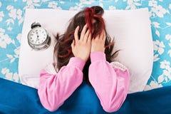 Chica joven enfadada por el despertador Foto de archivo