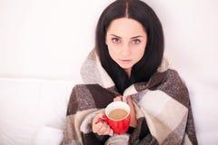 Chica joven enferma con la taza de consumición de la fiebre de té caliente Fotografía de archivo libre de regalías