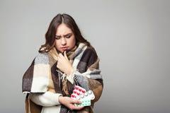 Chica joven enferma con las píldoras Imágenes de archivo libres de regalías