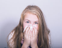 Chica joven enferma que sopla su nariz con el tejido de papel Fotografía de archivo libre de regalías