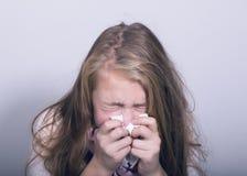 Chica joven enferma que sopla su nariz con el tejido de papel Imagen de archivo libre de regalías