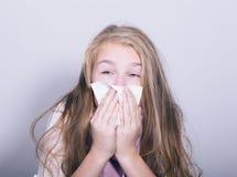 Chica joven enferma que sopla su nariz con el tejido de papel Fotos de archivo