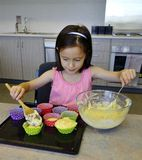Chica joven enfocada que cucharea la mezcla de la torta. Foto de archivo libre de regalías