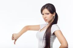 Chica joven enojada con el pulgar abajo en el estudio blanco del fondo Imagen de archivo libre de regalías