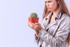 Chica joven enojada que presenta con el cactus en un fondo gris Fotografía de archivo