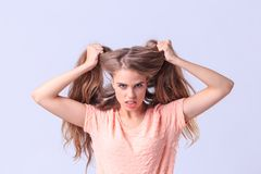 Chica joven enojada que presenta en estudio en un fondo gris Imagenes de archivo