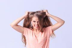Chica joven enojada que presenta en estudio en un fondo gris Imagen de archivo