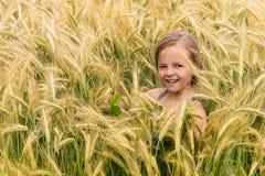 Chica joven entre los granos de maduración de un campo de trigo Imagen de archivo libre de regalías