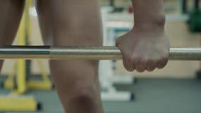 Chica joven, estructura atlética, entrenando en el gimnasio Ella va a la barra y la toma, para el ejercicio metrajes